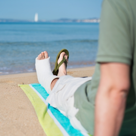 Injured Man with Plaster relaxing on Beach photo