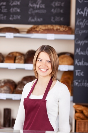 Friendly female worker in a bakery standing in front of loaves of bread with a beautiful smile photo