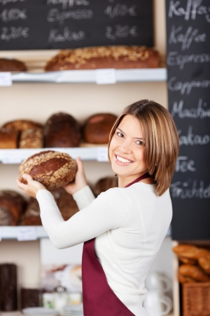 single shelf: Friendly worker in a bakery busy packing loaves of hand made specialist bread onto the shelves