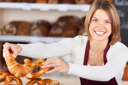 Friendly female worker in the bakery selecting rolls and croissants from a large wicker basket to serve to a customer photo