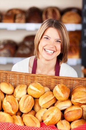 Smiling woman working in a bakery carrying a large flat wicker basket filled with crisp crusty golden rolls photo