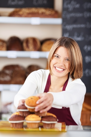 bake sale: Pretty smiling worker selecting muffins from a counter display in a modern bakery to sell to a customer