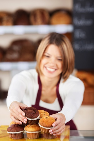 Bakery worker sorting the muffins on a counter display in a modern bakery photo