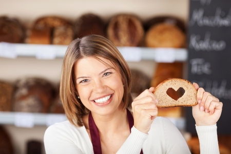 whole food: Happy woman showing bread with heart shape Stock Photo