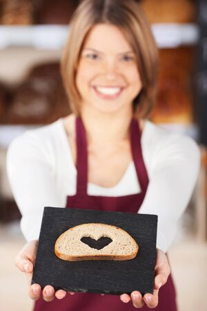 Pretty smiling bakery worker displaying a slice of bread with a heart shape cut out of the centre photo