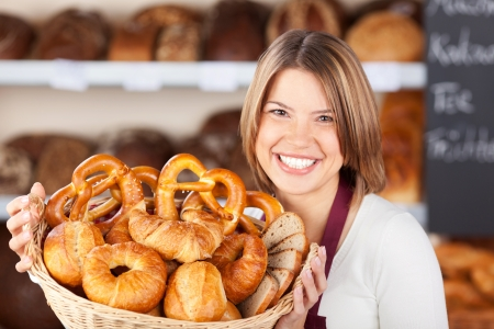 Smiling bakery assistant holding up a collection of assorted freshly baked rolls on display in a wicker basket
