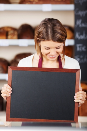 blank slate: Bakery worker holding up a blank slate or small chalkboard for your advertisement or text Stock Photo