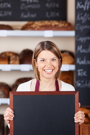 bakery shop: Smiling friendly bakery worker holding a blank chalkboard or slate with copyspace for your text