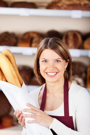 saleslady: Happy bakery worker with a bag of baguettes in her hand smiling at the camera Stock Photo