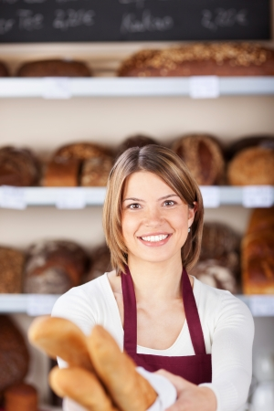 saleslady: Beautiful woman holding a bunch of baguette in bread store