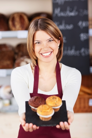 Female bakery worker with fresh muffins holding them out on a tray in front of her while smiling at the camera photo
