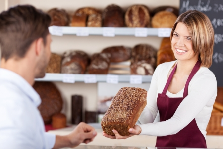 seller: Smiling friendly young bakery assistant selling bread showing a wholewheat loaf to a male customer