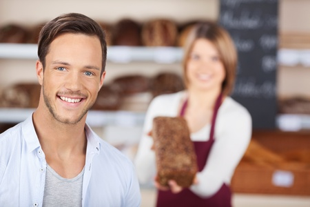 Female baker or saleswoman in her bakery with a male customer and fresh pastries or bakery products photo