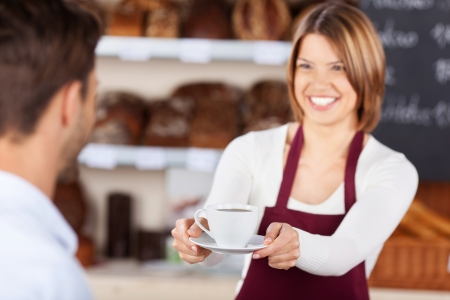 selling service smile: Bakery shopkeeper gives coffee to customer at the bread store