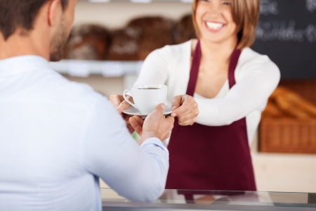 Female baker or saleswoman giving coffee to male customer inside the bread store