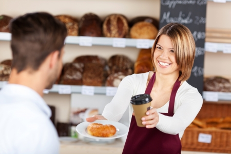 serving: Female baker giving coffee and croissant to male customer in the bread store