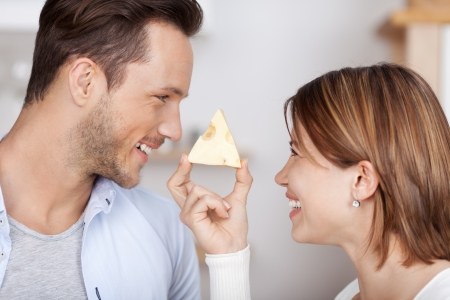 Smiling young couple with a piece of cheese Banco de Imagens