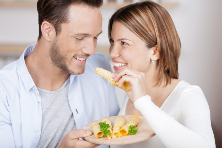 feed: Couple eats some cheese from a variety on plate