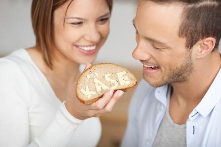 pareja comiendo: Feliz juguetón con la mujer que introduce una rebanada de pan con la palabra queso escrito en la lengua alemana hecha con queso de verdad