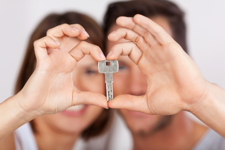 feeling: Young couple holding a house key together with their hands drawing a heart shape