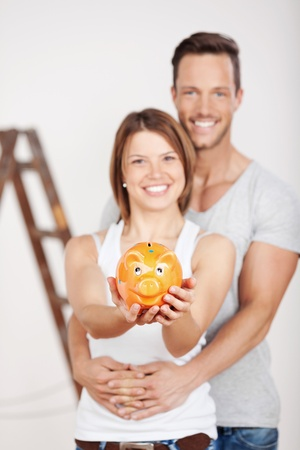 Conceptual portrait of young couple holding a piggybank at home photo