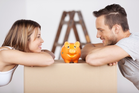 savings: New happy couple looking at the piggybank in a savings concept