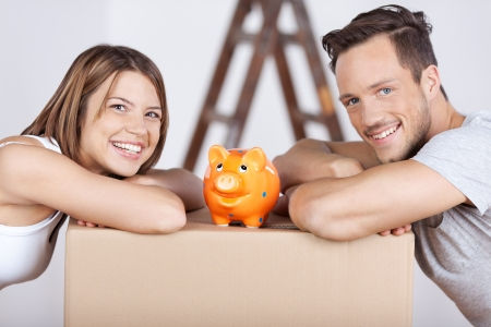 finance girl: Conceptual portrait of new couple with piggybank on top of the box