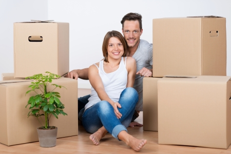 Happy couple sitting on the floor with boxes in their new house photo