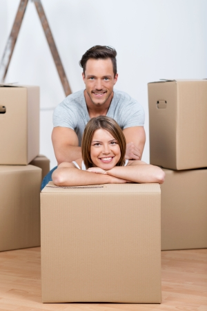 Smiling young couple sitting between many boxes in their new home photo