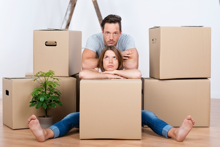 removals: Tired couple sitting between many boxes in their new home