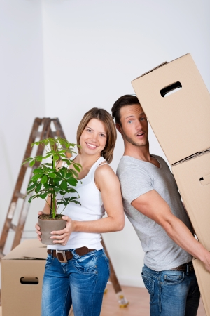Happy newly wed couple holding boxes and plant to fix their new home photo