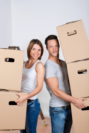 Portrait of beautiful couple with moving boxes isolated over white background