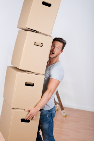Close up shot of a man holding a pile of boxes in his new home photo