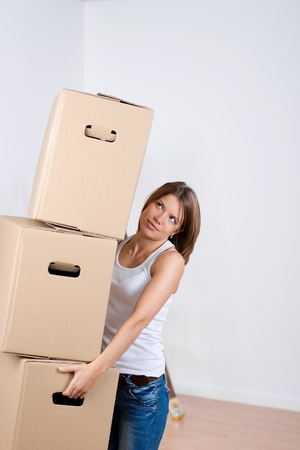 belongings: Woman carrying a stack of cardboard cartons as she packs up her household goods in preparation for moving