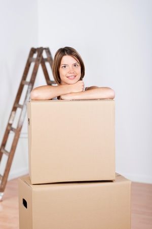 Beautiful woman with boxes and ladder at the background in her new home