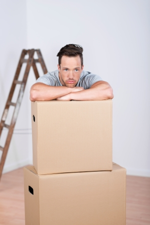 unmotivated: Depressed man leaning his chin on his arms on top of brown cardboard packing cartons when moving home