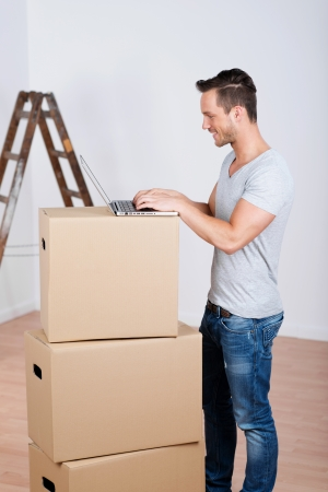 near side: Smiling man with boxes and laptop in his new home
