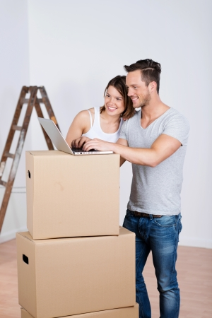 Happy loving couple with boxes and laptop in his new home photo