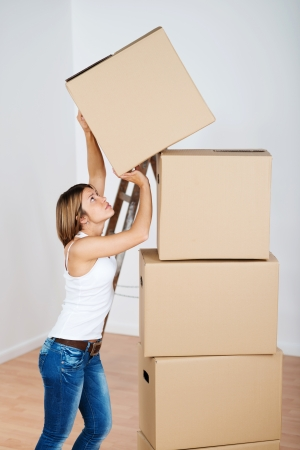 storage box: Pretty young woman stacking cardboard boxes packed with household goods when preparing to move home Stock Photo