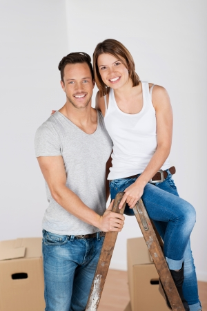 household goods: Happy couple packing up their household goods embracing while sitting on a ladder as they prepare to move home Stock Photo
