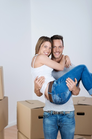 Loving man carrying his wife over the threshold of their new home into a room full of packed cartons photo