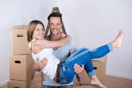 Sweet loving couple standing in their new house in a close up portrait photo