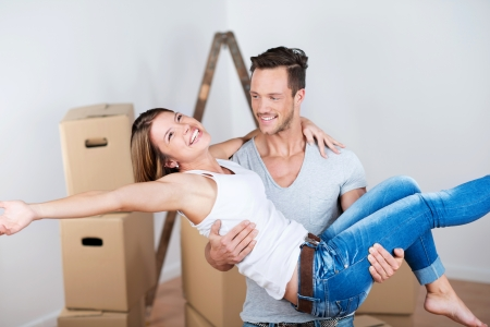 man carrying box: Joyful couple moving into their new home with the husband carrying his wife over the threshold Stock Photo