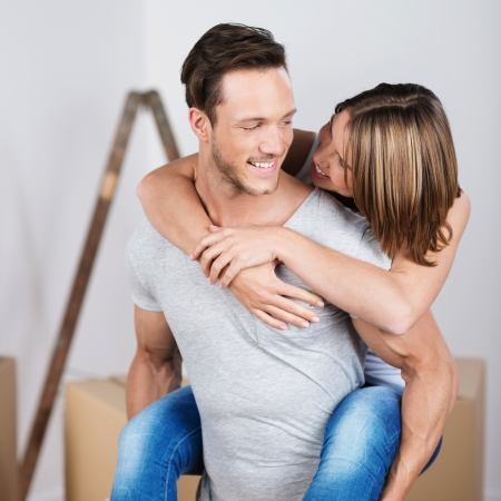 Happy young woman getting a piggyback ride from her husband in their new house photo