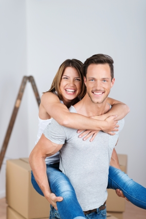 Portrait of a handsome young man giving a piggyback ride to his wife in their new house photo