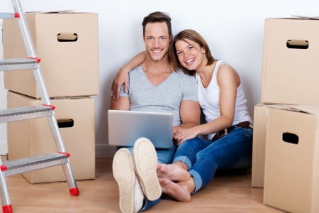 packaging move: Smiling couple using a laptop on the floor of their new home surrounded by stacks of brown cardboard packing cartons