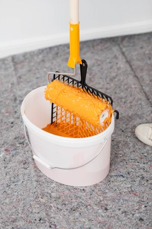 paintbucket: White bucket with orange paint and paint roller
