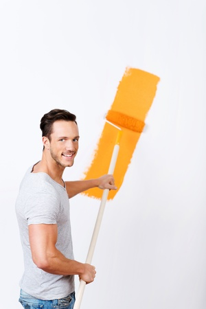 Young man painting a white wall orange using a roller on an extension handle when renovating his house Stock Photo - 21162095