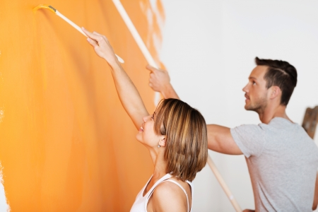 Young happy couple painting wall at new home in orange photo