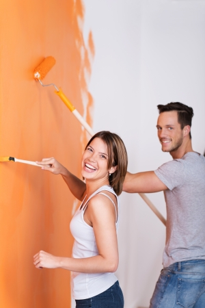 redecorating: Young couple having fun while painting the wall of their new home
